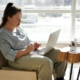Woman sitting by window with laptop