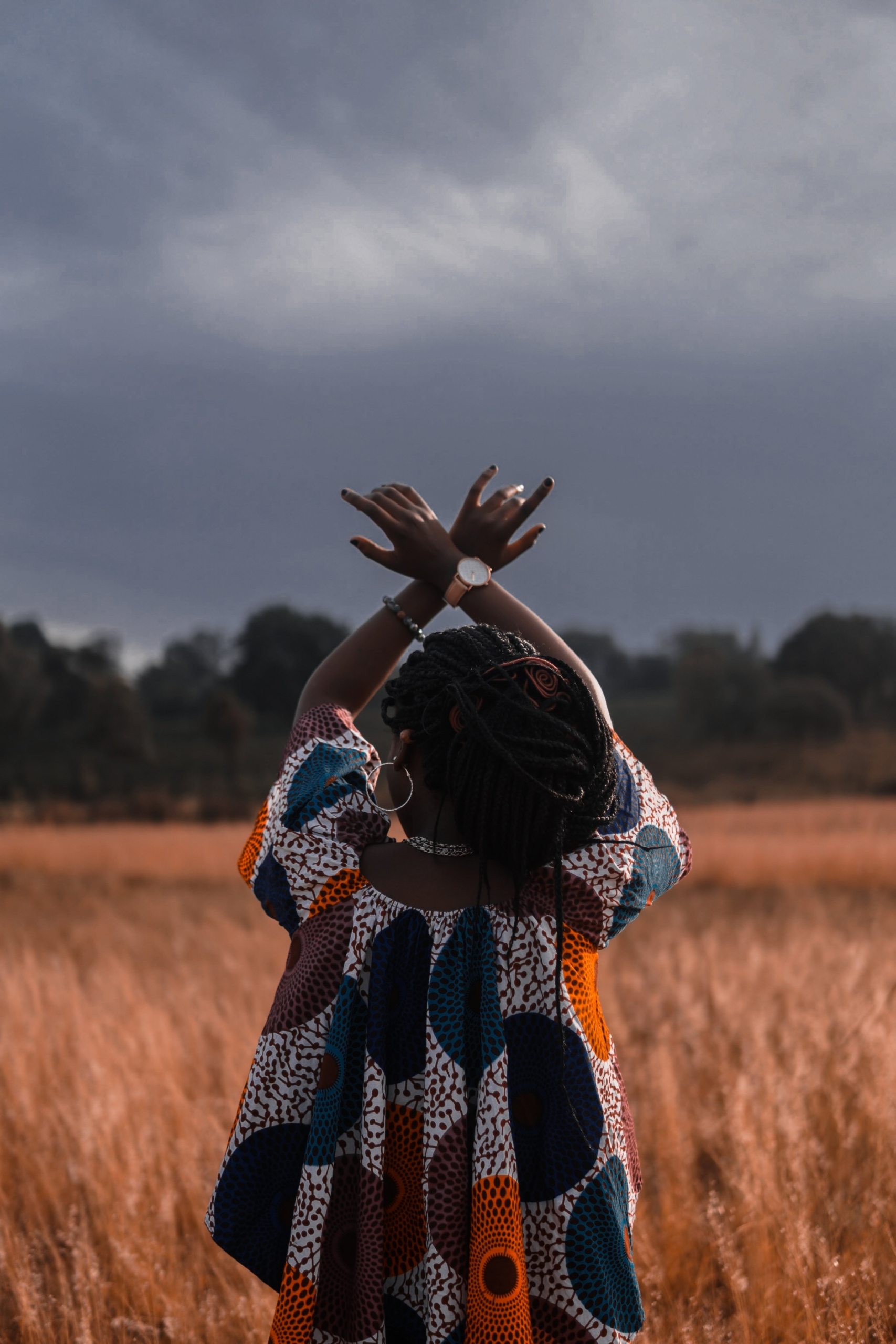 Woman in a field with hands raised